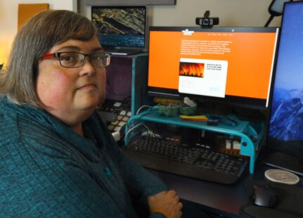 Photograph of Joan Donovan, a white woman, at her desk looking at a computer screen