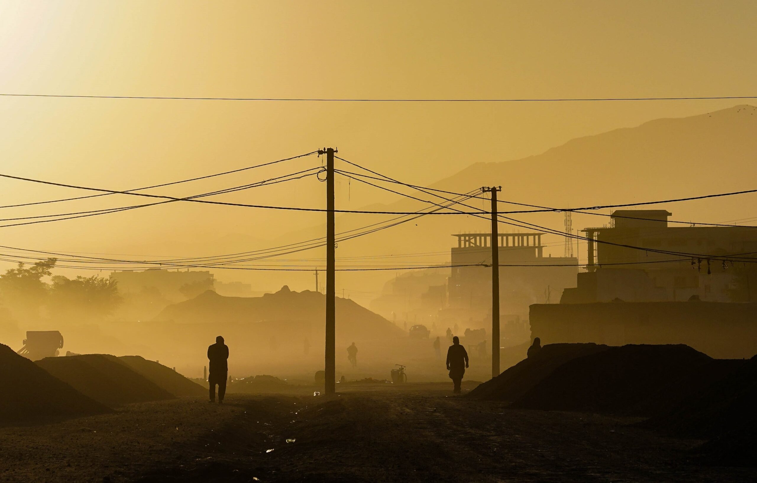 People walking down a street with wires strung above in the early morning